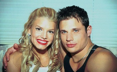 Jessica Simpson is smiling next to her boyfriend Nick Lachey, a 98 Degrees boys' band member.