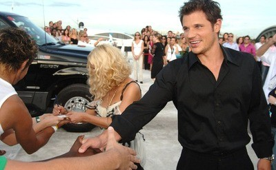 Jessica Simpson and Nick Lachey are signing autographs on the white carpet during the 2005 MTV Video Music Awards.